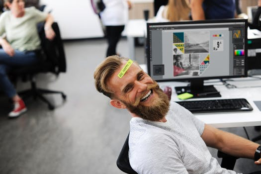 man at desk smiling and happy in 2018